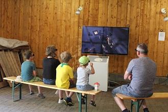 """Zuschauer betrachten einen großen Bildschirm der """"Virtuellen Limeswelten""""."""